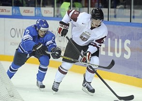 UFA, RUSSIA – DECEMBER 26: Latvia's Rinalds Rosinskis #5 skates with the puck while Finland's Miikka Salomaki #22 stick checks during preliminary round action at the 2013 IIHF Ice Hockey U20 World Championship. (Photo by Richard Wolowicz/HHOF-IIHF Images)